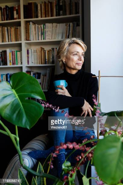 mature woman drinking coffee and relaxing at home - cosy stock pictures, royalty-free photos & images