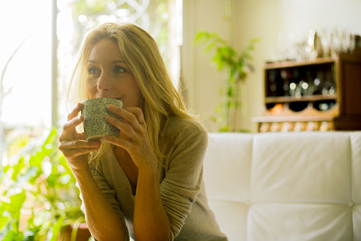 Mature woman drinking coffee at home - gettyimageskorea