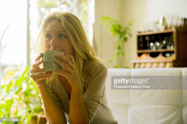 mature woman drinking coffee at home - one mature woman only stock-fotos und bilder