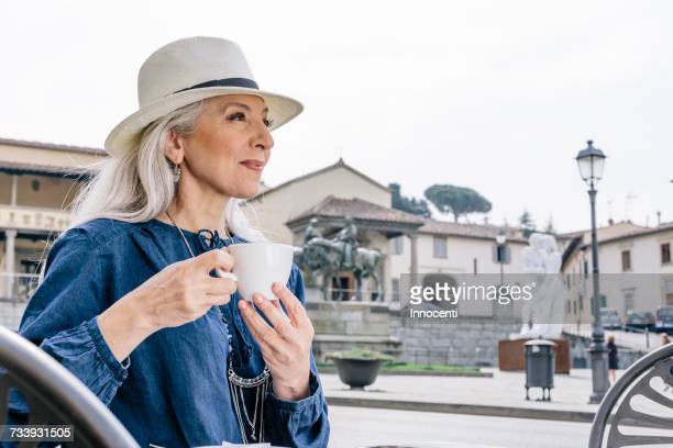 Mature woman drinking coffee at sidewalk cafe, Fiesole, Tuscany, Italy