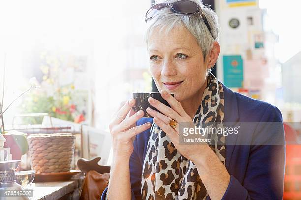 mature woman drinking coffee in cafe