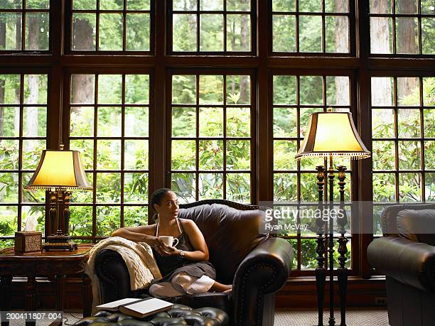 mature woman drinking coffee on leather armchair in lobby of lodge - ロビー ストックフォトと画像