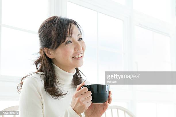 A mature woman drinking coffee