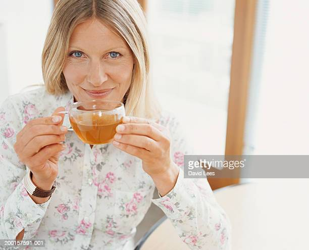 Mature woman drinking tea, smiling, portrait