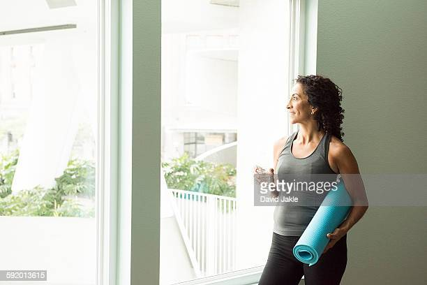 Mature woman drinking water after yoga