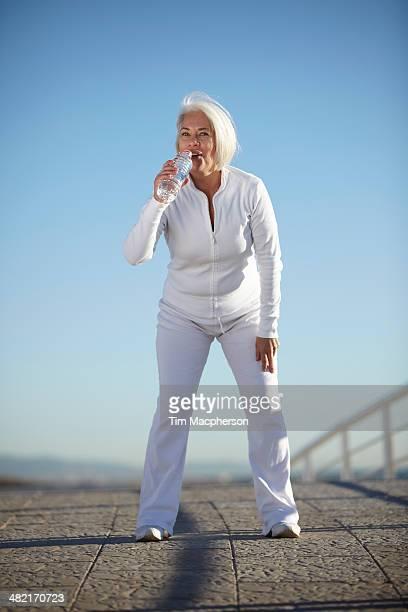 mature woman drinking water on walk - white pants fotografías e imágenes de stock