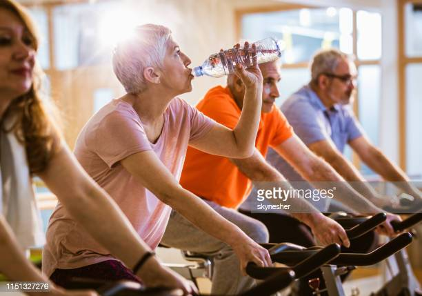 Mature woman drinking water while exercising on stationary bike in health club.
