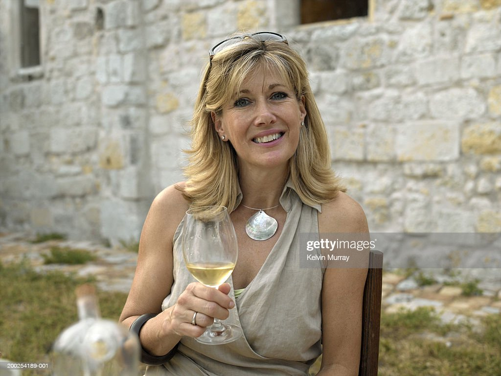 mature woman drinking wine at outdoor table smiling portrait stock