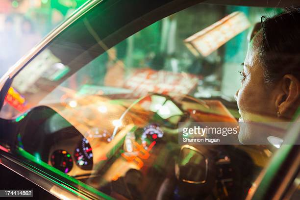 Mature Woman Driving Car, City Lights Reflected