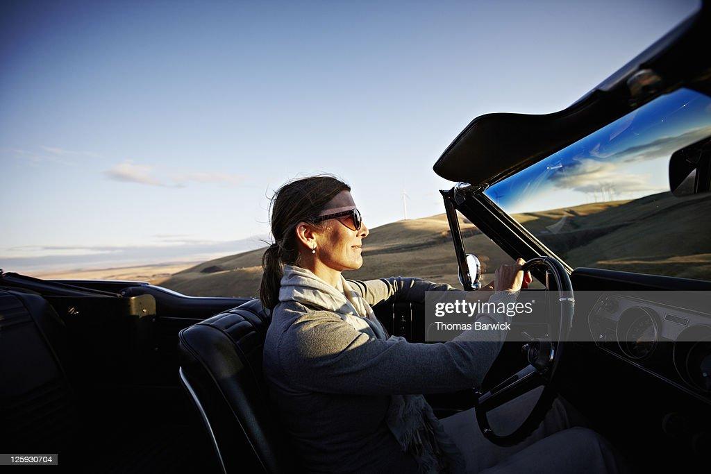Mature woman driving convertible at sunset : Stock Photo