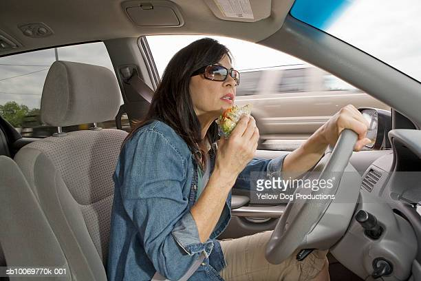 Mature woman driving on highway while eating sandwich