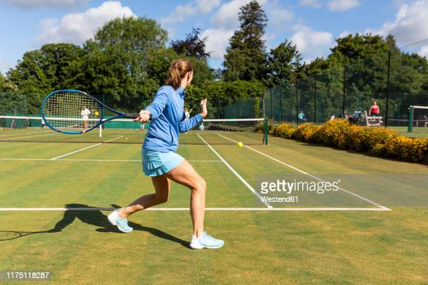 mature woman during a tennis match on grass court - tennis stock-fotos und bilder