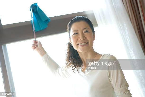 Mature woman dusting window, smiling