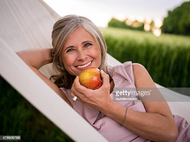 Mature woman eating a fresh apple while relaxing outdoors