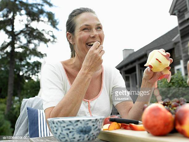 Mature woman eating apple, smiling