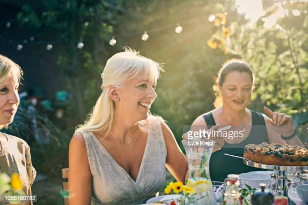 Mature woman eating at dinner party in garden