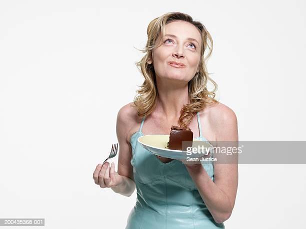 Mature woman eating chocolate cake, close-up