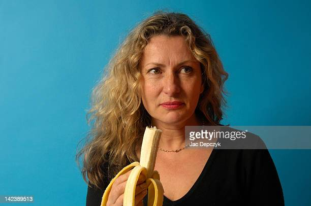 mature woman eating ripe banana - depczyk stock pictures, royalty-free photos & images