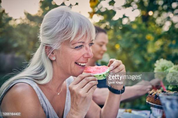 Mature woman eating water melon
