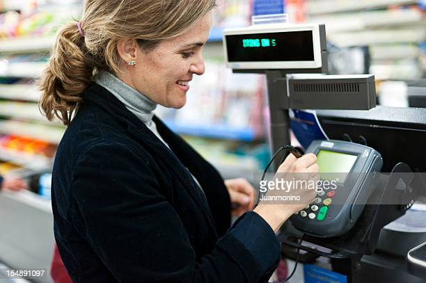 mature woman electronic signing her bill - convenience store counter stock photos and pictures