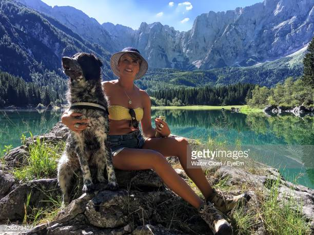 Mature Woman Embracing Dog While Sitting On Rock Against Mountains
