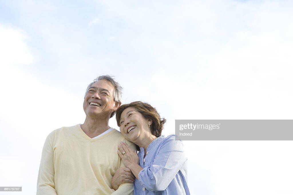 Mature woman embracing man, smiling : Stock Photo