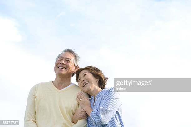 Mature woman embracing man, smiling
