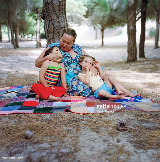 Mature woman embracing two girls (3-5) on blanket in forest