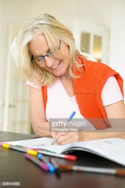 mature woman enjoying adult colouring book - colouring bildbanksfoton och bilder