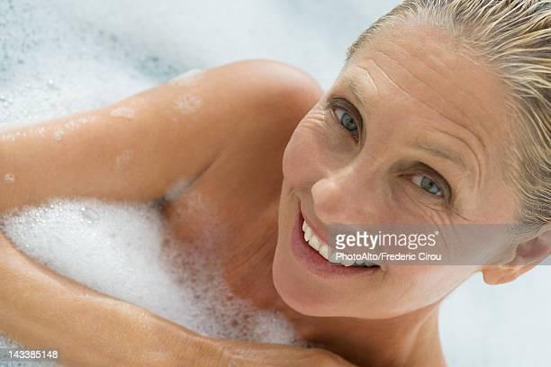 Mature woman enjoying bubble bath, tilt