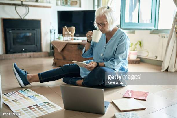 mature woman enjoying coffee and plans for home improvement - mid length hair stock pictures, royalty-free photos & images