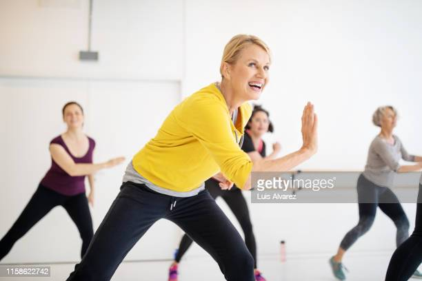 mature woman enjoying dancing at fitness studio - 50 59 years stock pictures, royalty-free photos & images