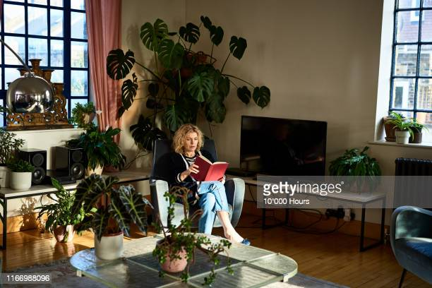 mature woman enjoying her book in boho living room - reading stock pictures, royalty-free photos & images