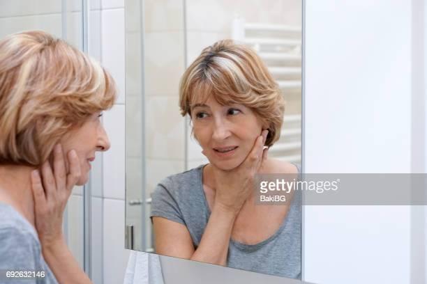 熟女の鏡に彼女の顔を調べる
