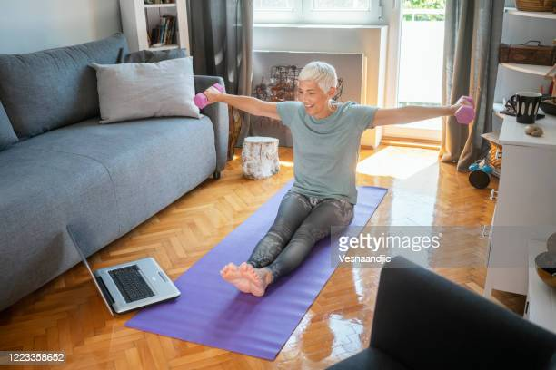 mature woman exercise at home - trainold stock pictures, royalty-free photos & images