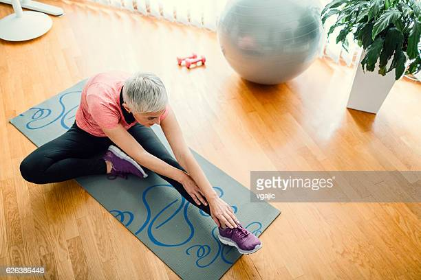 mature woman exercise at home. - older woman legs stock photos and pictures