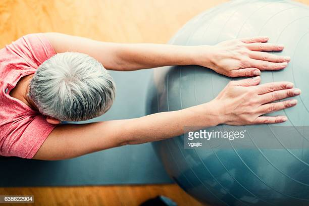 mature woman exercise at home. - pilates foto e immagini stock