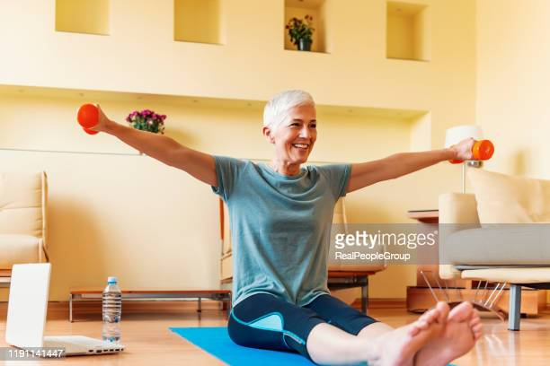 mature woman exercise at home. portrait of senior woman lifting dumbbells. happy senior woman making fitness training with dumbbells - home workout stock pictures, royalty-free photos & images