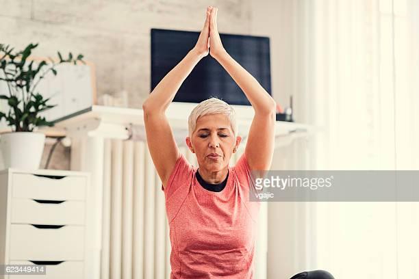 mature woman exercises yoga in her livingroom. - lotuspositie stockfoto's en -beelden