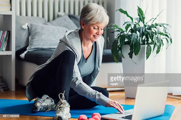 Mature Woman Exercising At Her Home.