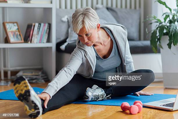 mature woman exercising at home. - mature women stock pictures, royalty-free photos & images