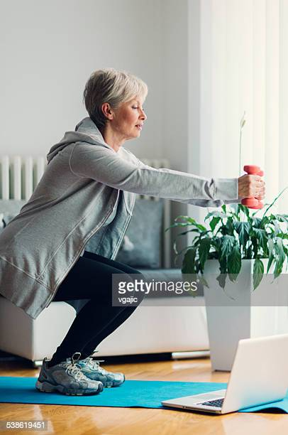 mature woman exercising at home. - hurken stockfoto's en -beelden