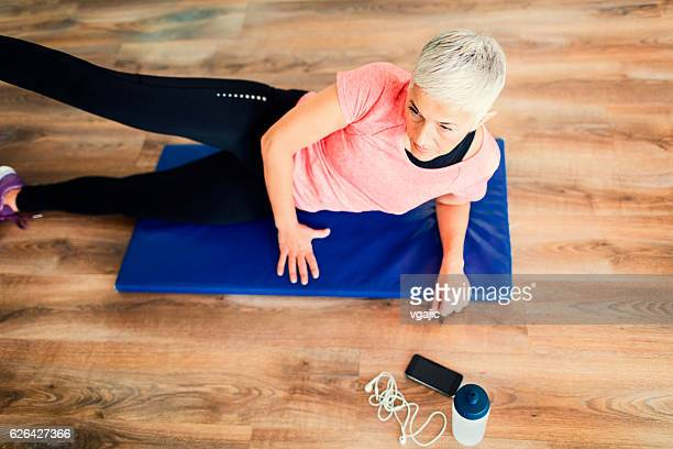 mature woman exercising in gym. - older woman legs stock photos and pictures