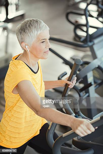 Mature Woman Exercising In Gym.