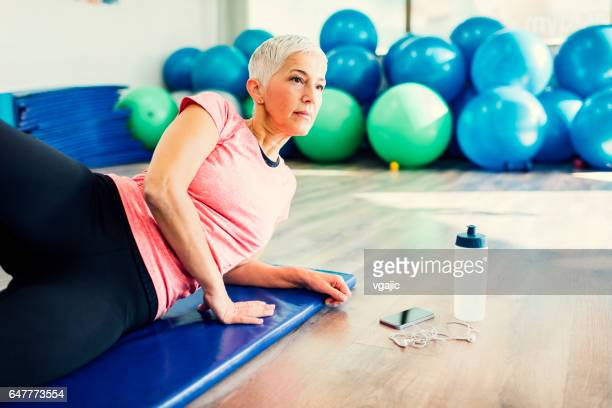 mature woman exercising in gym - lying on side stock pictures, royalty-free photos & images