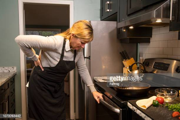 a mature woman experiencing backache at home in the kitchen - back pain stock pictures, royalty-free photos & images