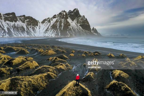 mature woman exploring stokksnes with vestrahorn mountain in the background - iceland stock pictures, royalty-free photos & images