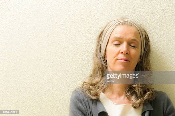 Mature woman eyes closed dreaming serenity leaning content