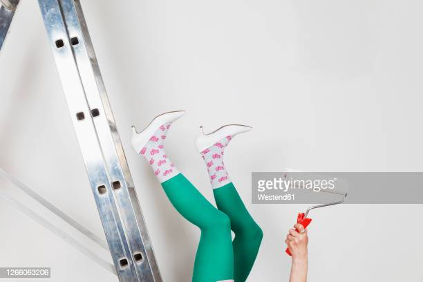 mature woman falling from ladder during painting walls at home - emergencies and disasters stock pictures, royalty-free photos & images