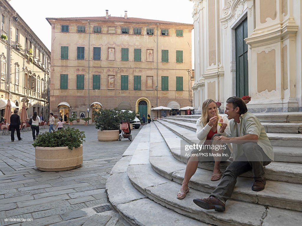 Mature woman feeding ice cream to man on steps : Bildbanksbilder